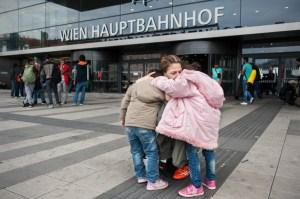 Aysha abraça suas duas filhas na entrada principal da estação central de Viena, depois de esperar na fila do bilhete por horas. Foto de Georgios Makkas