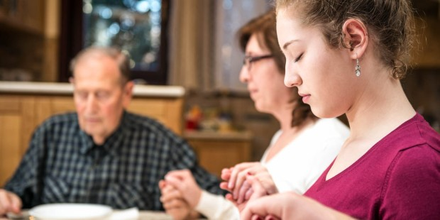 FAMILY PRAYING AT DINNER