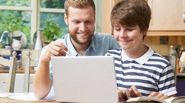 Tutor Helping Teenage Boy With Studies