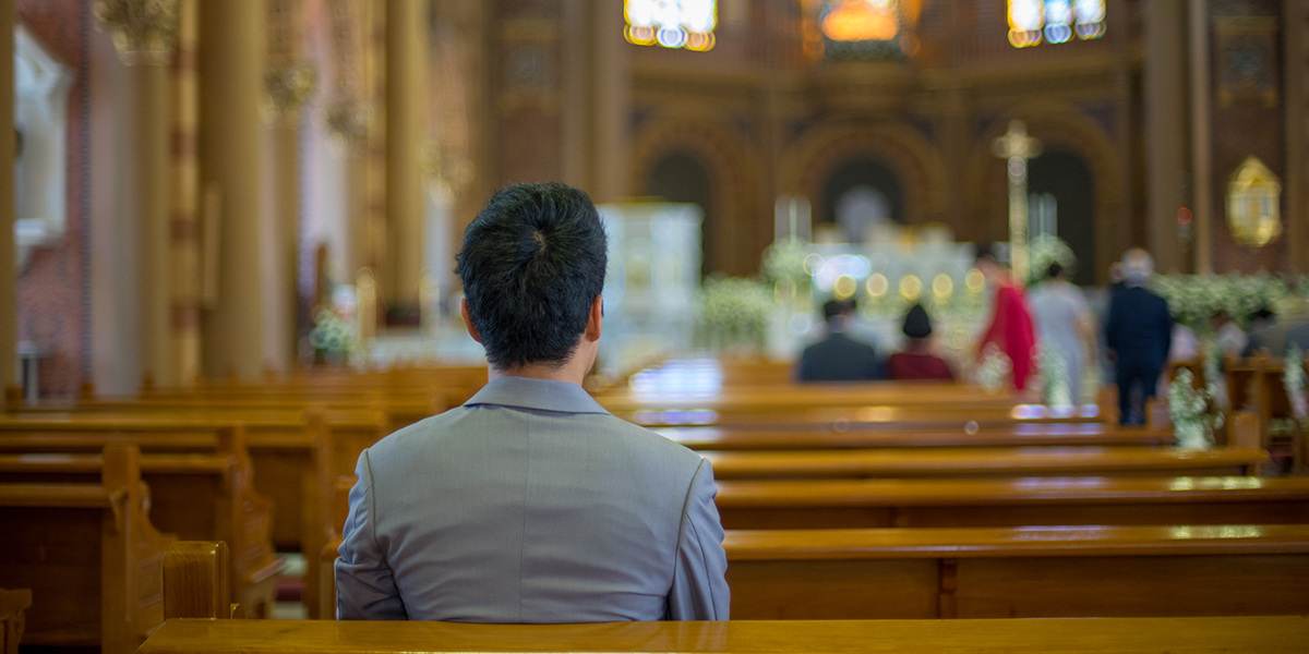 ASIAN MAN PRAYING IN CHURCH