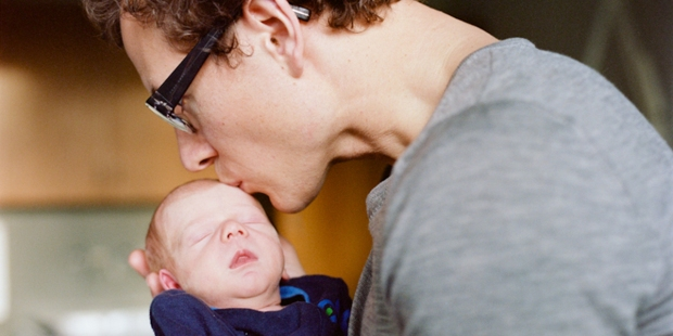 FATHER KISSING NEWBORN