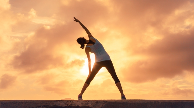 WOMAN,STRETCHING,SUNSET