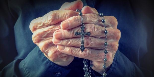 Pessoa idosa rezando o terço