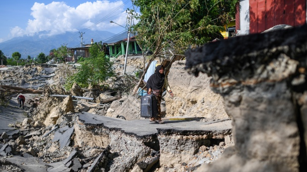 INDONESIA PALU / A woman with a suitcase makes her way along a destroyed road in Palu, Indonesia's Central Sulawesi on October 2, 2018, after an earthquake and tsunami hit the area on September 28. The bodies of dozens of students have been pulled from their landslide-swamped church in Sulawesi, officials said on October 2, as an international effort to help nearly 200,000 Indonesia quake-tsunami victims ground into gear. / AFP PHOTO / Jewel SAMAD