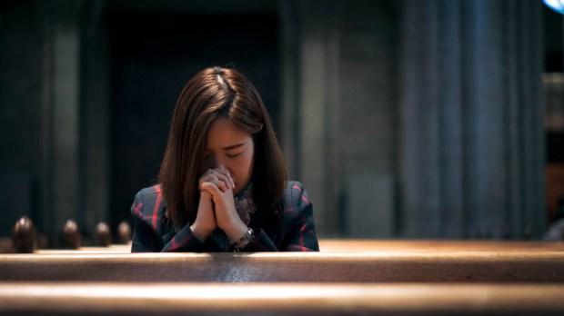 WOMAN PRAYING,CHURCH PEWS