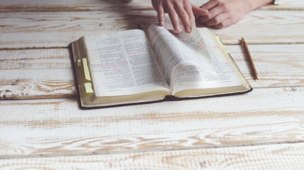 Biblia otwarta na drewnianym stole