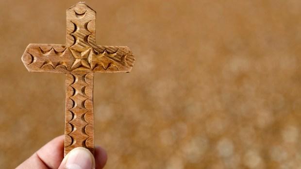 main tenant une croix