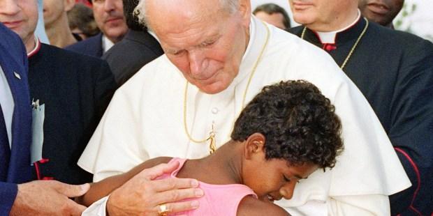 Uma criança abraça o Papa João Paulo