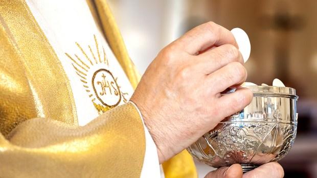 Eucaristia: um padre e a comunhão