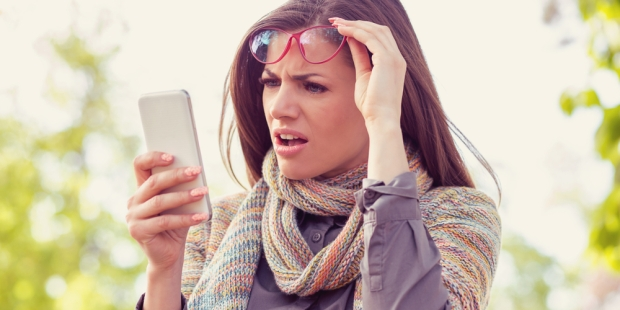 WOMAN LOOKING AT PHONE CONFUSED