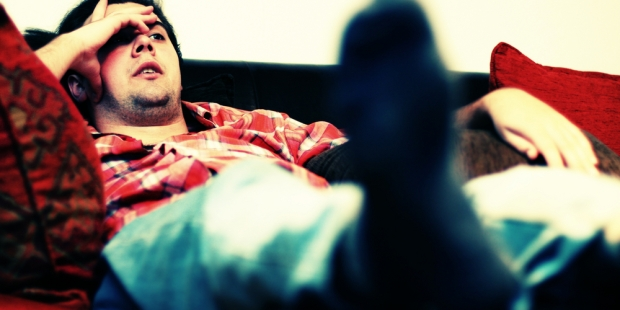 Lazy man chilling out on sofa watching tv
